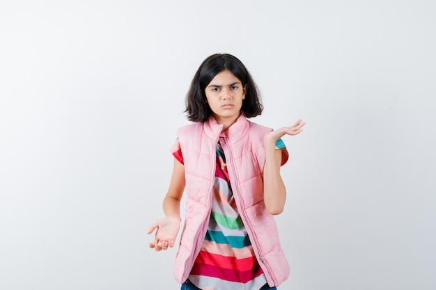 Menina, esticando as mãos questionando de maneira em t-shirt, colete baiacu, jeans e parecendo confusa. vista frontal.