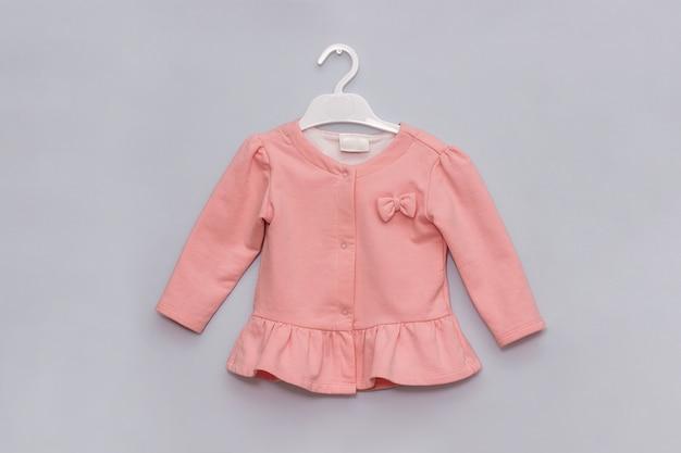 Menina estilo olhar. casaco elegante rosa pastel no cabide. conceito de roupas de moda infantil feminino