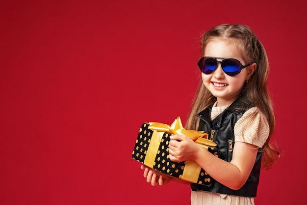 Menina estilosa com uma caixa de presente
