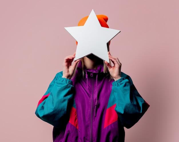 Menina estilosa em um traje esportivo dos anos 80 segurando um banner em forma de estrela na parede rosa