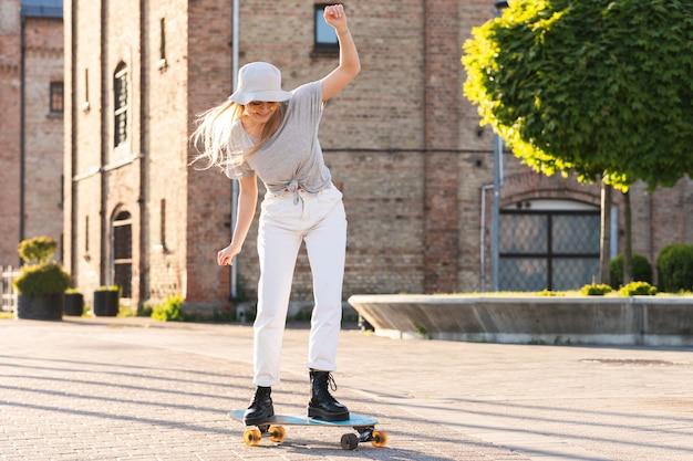 Menina estilosa tentando andar de longboard