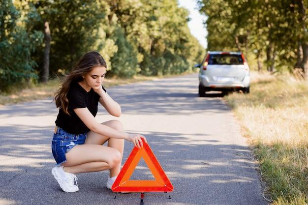 Menina estressada, colocando o sinal de emergência na estrada