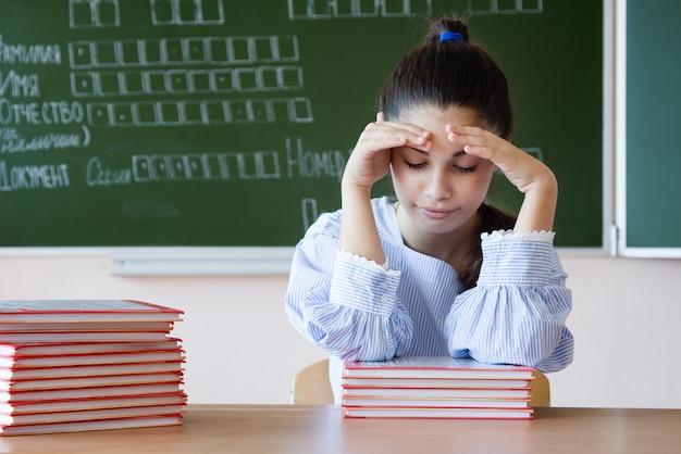 Menina estressada em copos senta-se contra o quadro-negro em sala de aula