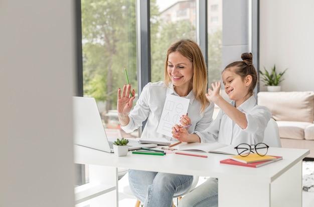 Menina estudando com seu professor dentro de casa