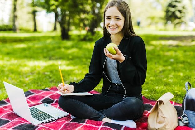 Menina estudando e comendo uma maçã