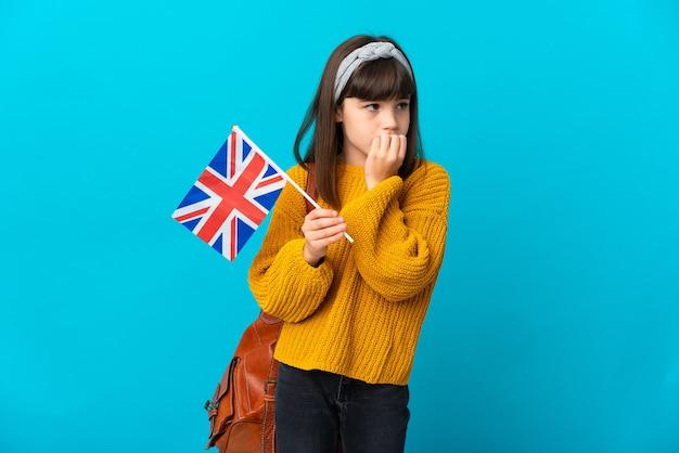 Menina estudando inglês isolada em um fundo azul, tendo dúvidas