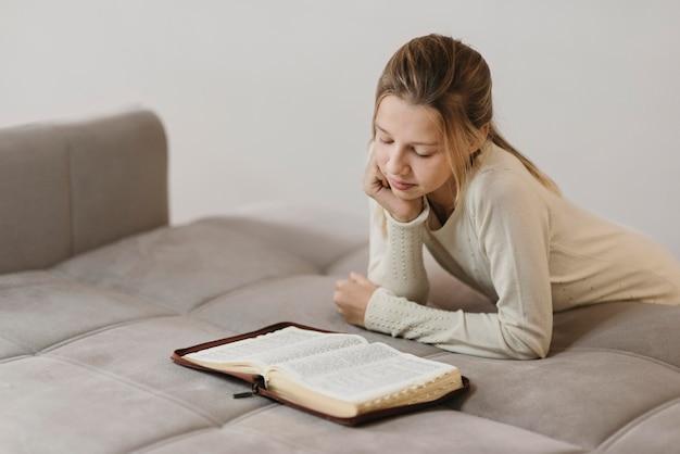 Menina estudando um livro sagrado