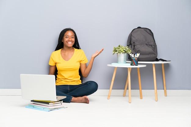 Menina estudante adolescente sentado no chão segurando copyspace imaginário na palma da mão