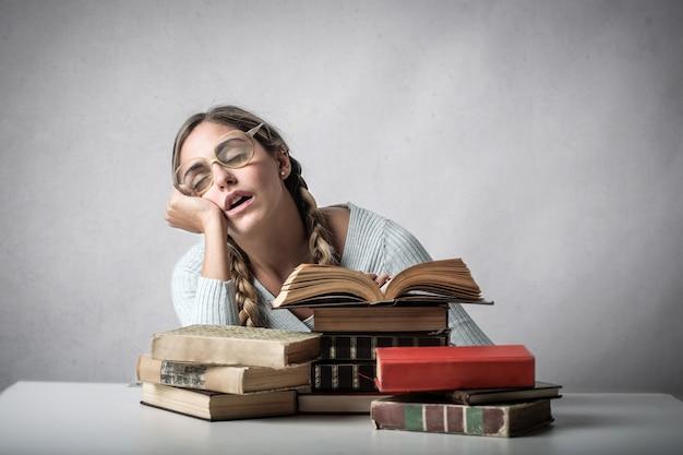 Menina estudante adormecer em livros