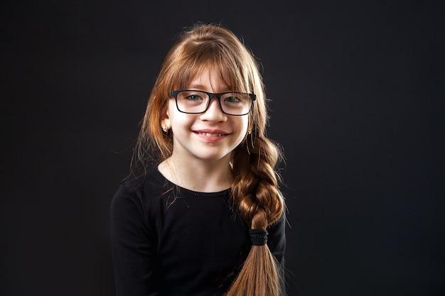 Menina, estudante em copos com pigtail sorrindo no estúdio em um fundo preto