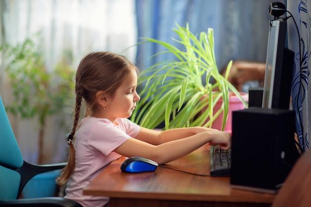 Menina estudante está sentado em casa em uma mesa de computador e está envolvido em um computador desktop.