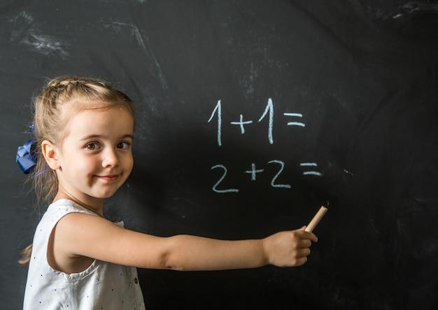 Menina estudante perto de quadro-negro