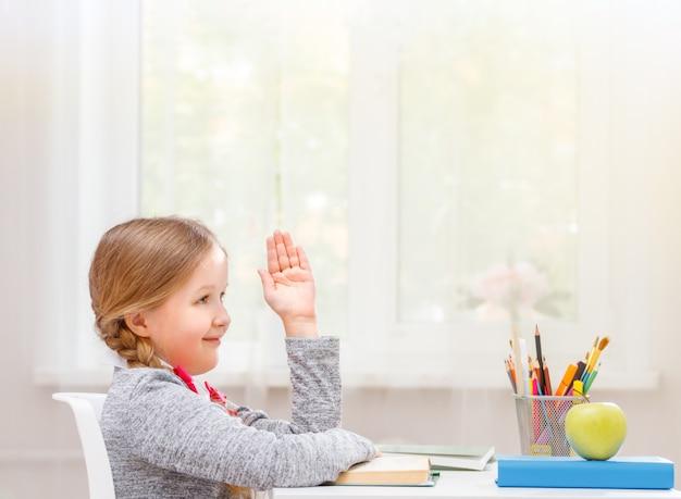 Menina estudante sentado à mesa e puxa a mão para cima.