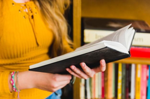 Menina, estudar, livro interessante, em, prateleiras