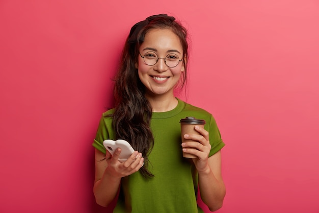 Menina étnica adorável positiva rola fotos no smartphone, usa smartphone moderno e bebe café para viagem, se sente tocada e encantada, usa óculos redondos, usa o site de compras