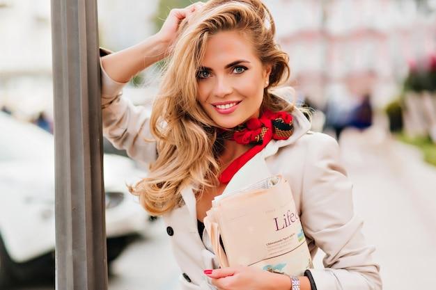 Menina europeia animada com cabelo loiro encaracolado rindo apoiada em um pilar de ferro em um dia ensolarado