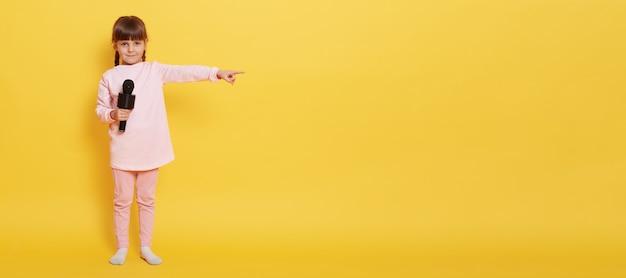 Menina europeia com microfone olha para a câmera enquanto segura o microfone, aponta o dedo indicador de lado para o espaço vazio para propaganda ou promoção, charmosa vocalista apresentando algo na parede amarela.