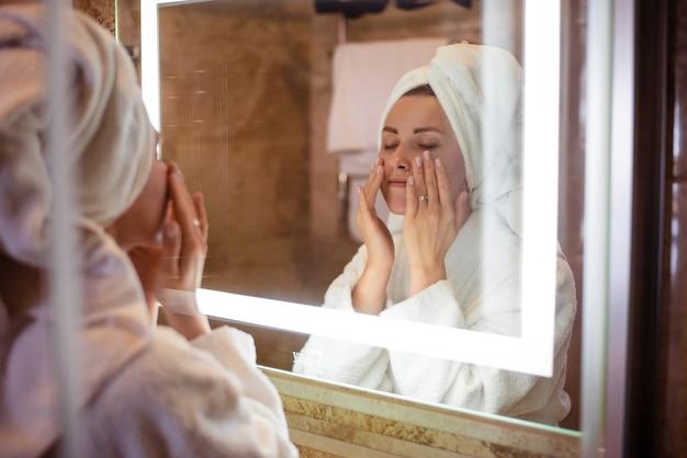 Menina europeia com os olhos fechados, aplicando creme cosmético no rosto. jovem e linda mulher usa roupão de banho e toalha de banho embrulhada na cabeça. rosto de senhora no espelho. conceito de cuidados com a pele do rosto