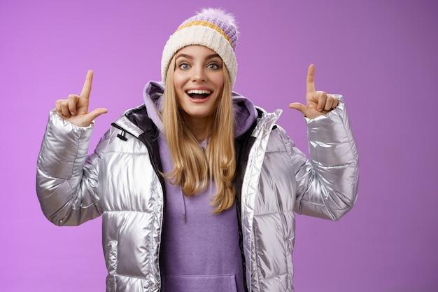 Menina europeia de cabelos louro, animada e despreocupada, com jaqueta prata e chapéu de inverno levantando as mãos