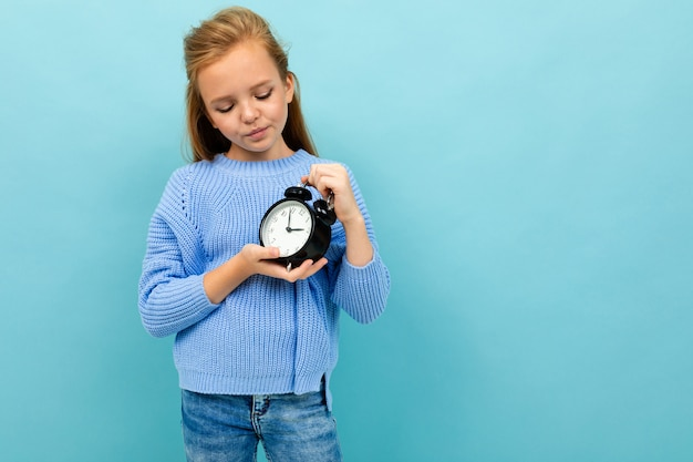 Menina europeia descontente olha para a hora do alarme em azul claro