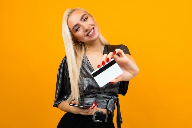 Menina europeia detém um telefone e um cartão de crédito com uma maquete na parede amarela