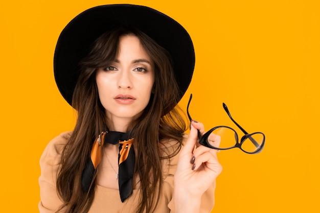 Menina europeia elegante em um fundo laranja com óculos para visão nas mãos