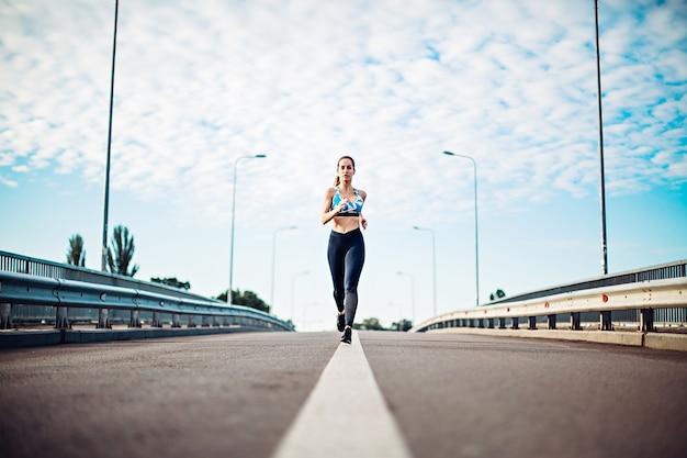 Menina européia no sportswear correndo na linha rodoviária