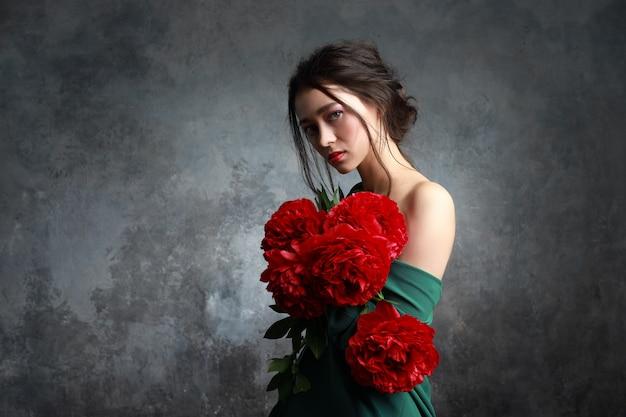 Menina européia nova bonita que olha asiática com flores do peão