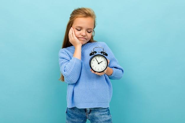 Menina europeia olha para um despertador na parede azul claro