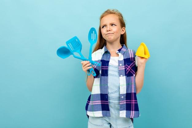 Menina européia pensativa, segurando um forno, luvas e talheres nas mãos na parede azul clara