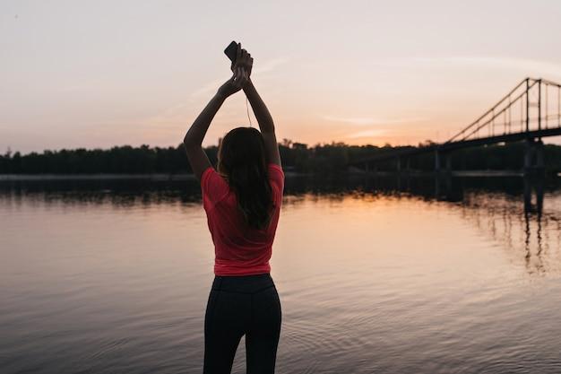Menina europeia refinada em t-shirt rosa relaxando após o treinamento ao ar livre. retrato de mulher fascinante, apreciando a vista do nascer do sol.