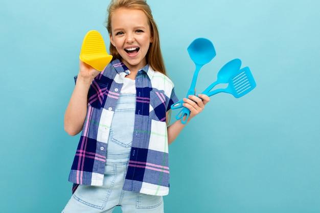 Menina europeia sorridente com utensílios de cozinha em mãos na parede de azul claro