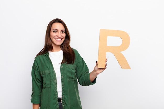 Menina excitada segurando a letra r do alfabeto para formar uma palavra ou uma frase