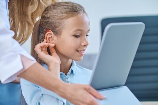 Menina experimentando aparelho auditivo em frente ao espelho