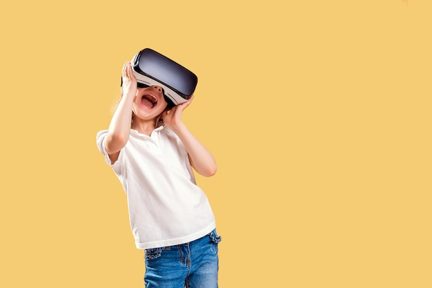 Menina experimentando jogo de fone de ouvido vr amarelo. emoções surpreendidas em seu rosto. criança usando um dispositivo de jogos para realidade virtual.