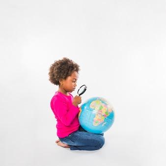 Menina, explorando, globo, com, lupa, em, estúdio