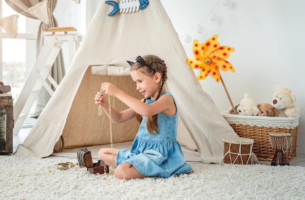 Menina explorando joias em um pequeno baú sentada no chão do quarto em frente à cabana