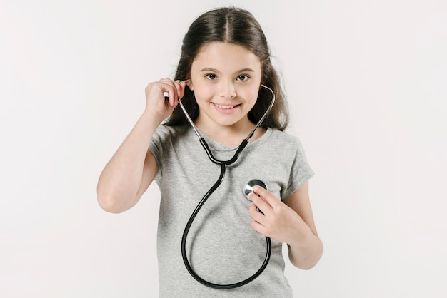 Menina, explorando o batimento cardíaco com estetoscópio