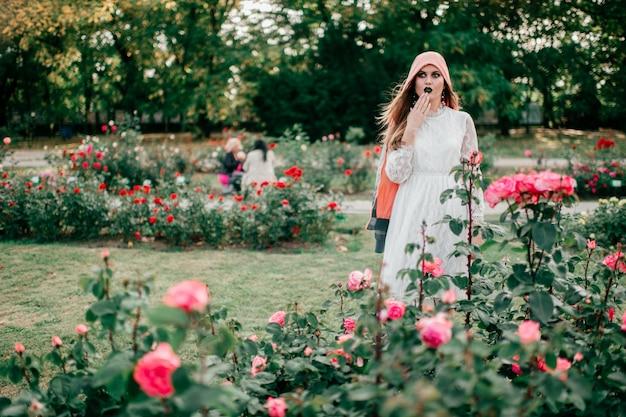 Menina expressiva com gótico compõem retrato ao ar livre no parque ensolarado
