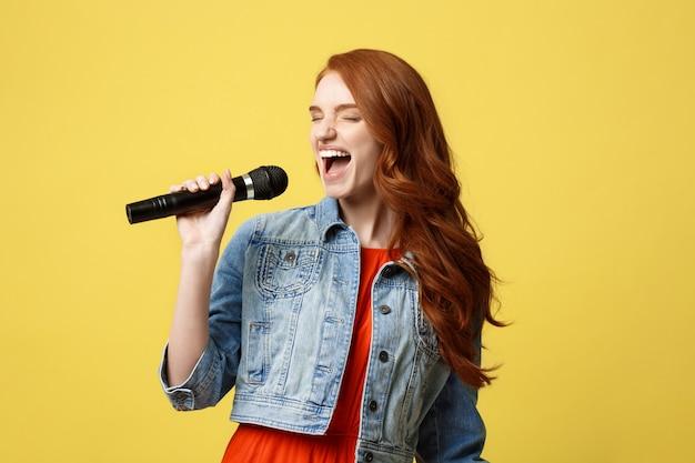 Menina expressivo que canta com um microfone, fundo amarelo brilhante isolado.