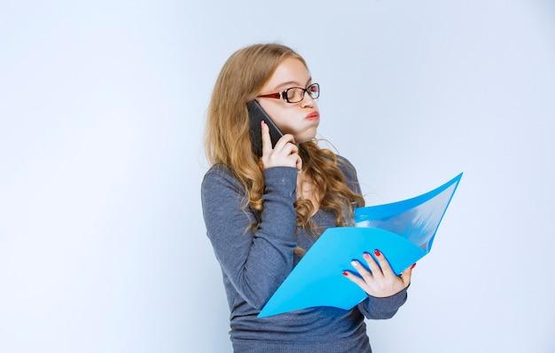 Menina falando ao telefone de forma insatisfeita e fazendo correções na pasta azul.