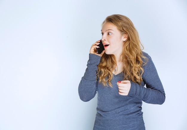 Menina falando ao telefone e ficando surpresa.