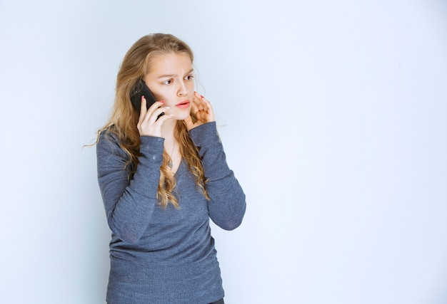 Menina falando ao telefone e parece apavorada.