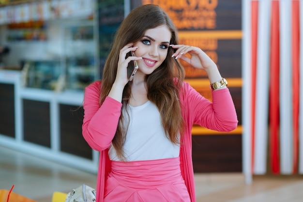 Menina falando ao telefone enquanto sorri e que toca a cabeça