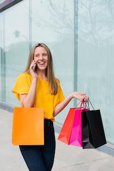 Menina falando ao telefone, segurando sacolas de compras