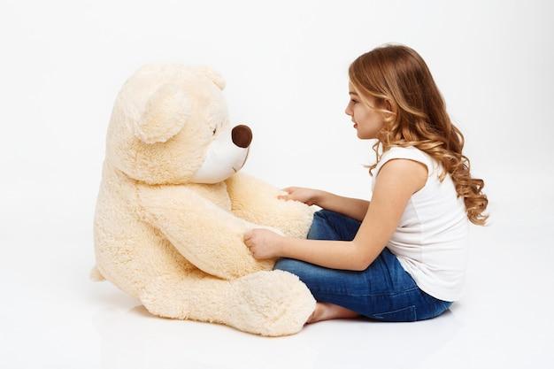 Menina falando com urso de brinquedo, pois é um amigo.