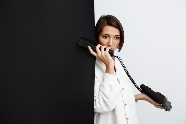 Menina falando no telefone antigo sobre parede preto e branco
