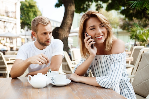 Menina falando no telefone enquanto o namorado dela está entediado.