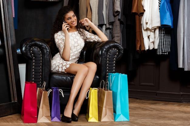 Menina falando no telefone, sentado no shopping com as compras.