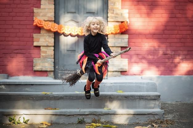 Menina fantasiada de bruxa comemorar o halloween ao ar livre e se divertir.